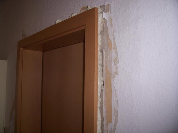Verputzen um eingebaute Holztür bei schiefer Wand. Zieht Holztür ...